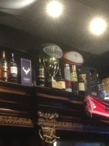 a couple of rugby balls on top of trophies